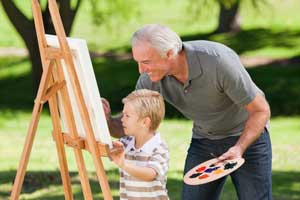 Grandfather and grandson painting outside