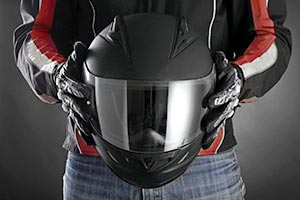 A biker holding a protective helmet
