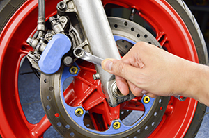 Man with cresent wrench working on red motorcycle wheel