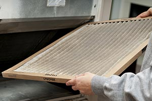 A person replacing a furnace filter