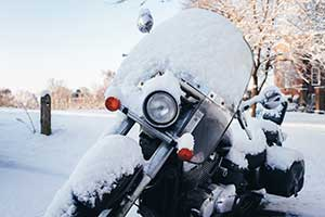 Motorcycle parked outside and covered in snow