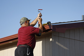 A mobile home owner caulking a gutter