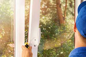Man with blue ball cap and screw driver in hand putting a replacement window in place