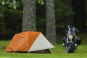 Motorcycle parked next to tent on the edge of the woods