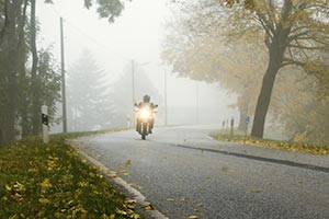 A motorcycle rider driving in a light fog