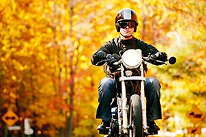 Motorcycle riding down road with leaves and fall colors in the background