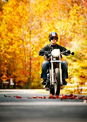 A biker riding through fall leaves on road