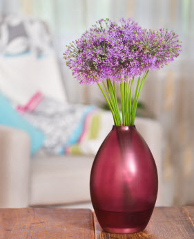 A vase of fresh purple flowers sitting on a table
