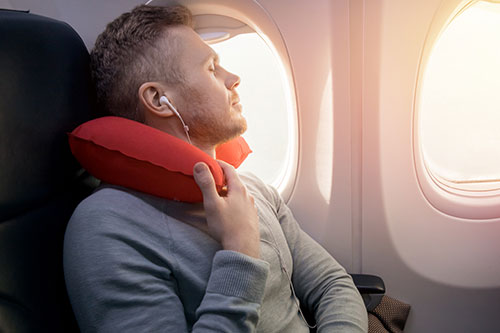 A person relaxing with music while in plane